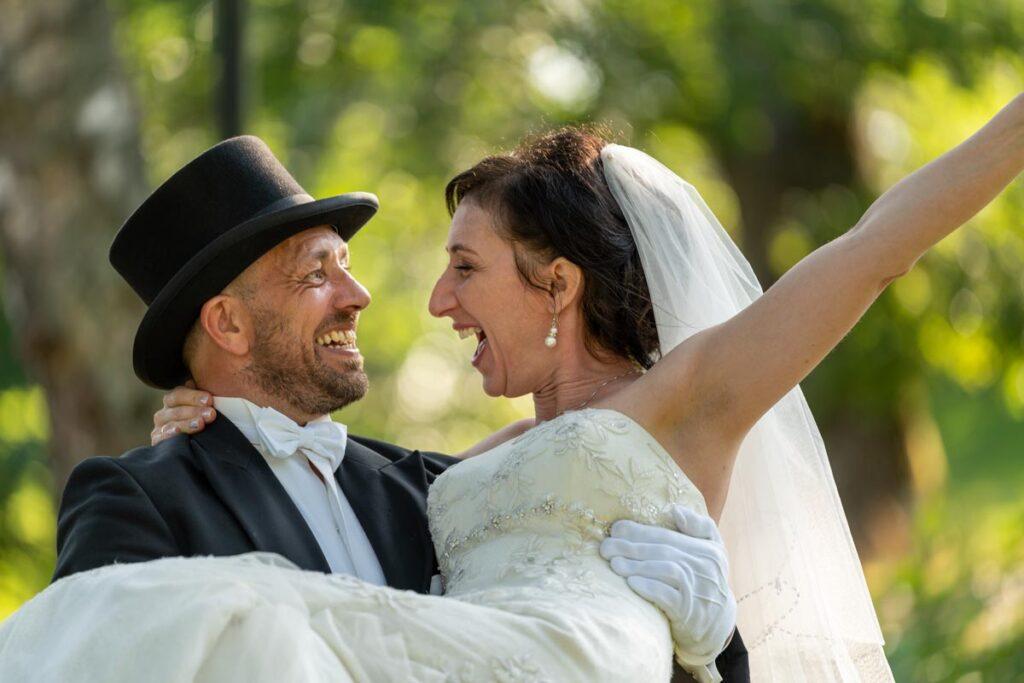 Brudgummen lyfter bruden som sträcker armarna i luften