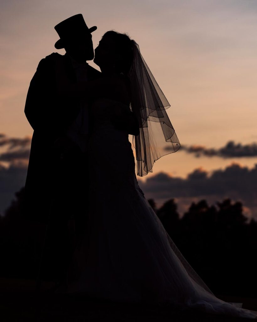 Brudpar håller om varandra i solnedgången
