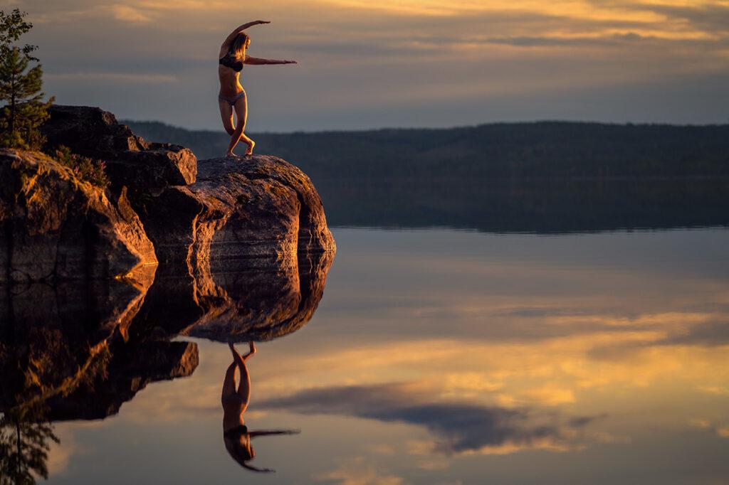 kvinna dansar på stor sten vid sjön