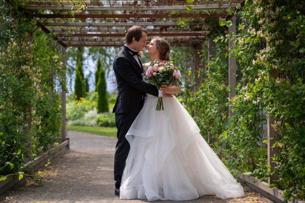 Bröllopspar håller om varandra i en pergola