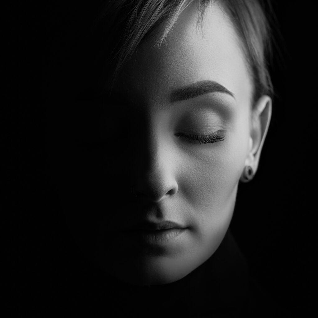 svart vitt porträtt av kvinna med halva ansiktet i ljus och halva ansiktet i mörker