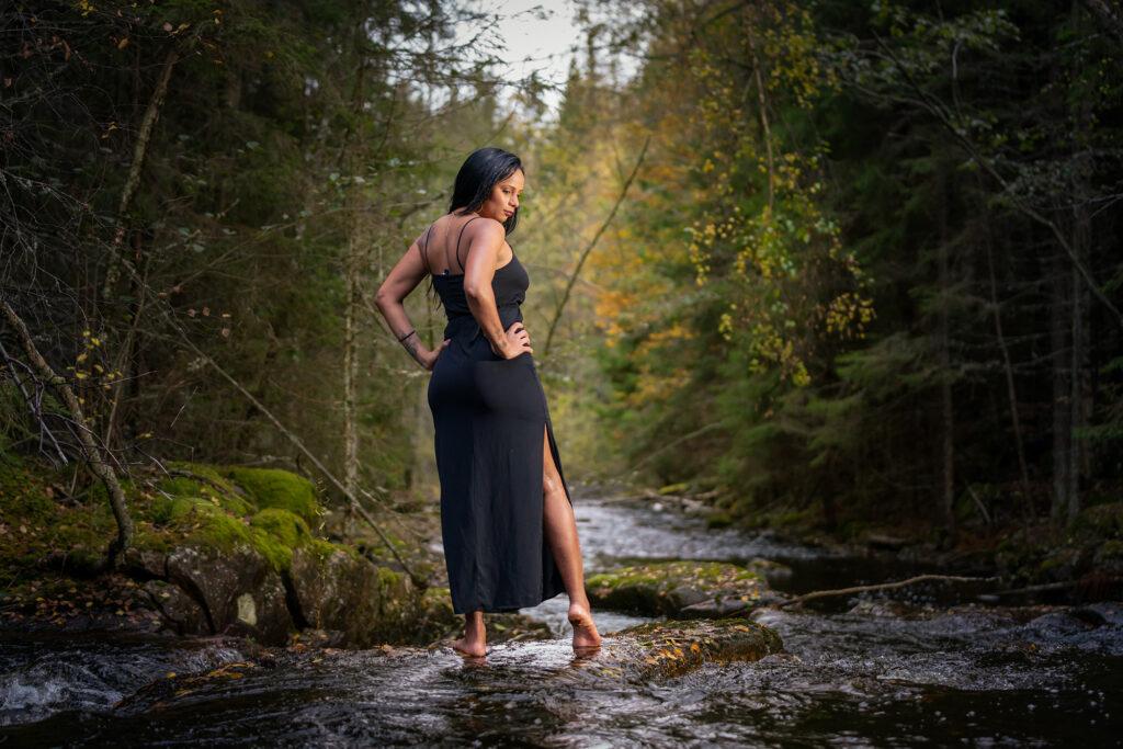 kvinna i svart kjol står på en sten i en bäck