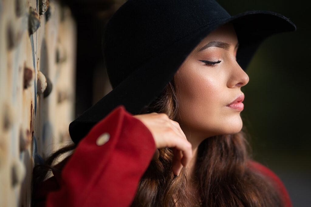 profil bild av kvinna i svart hatt och röd rock