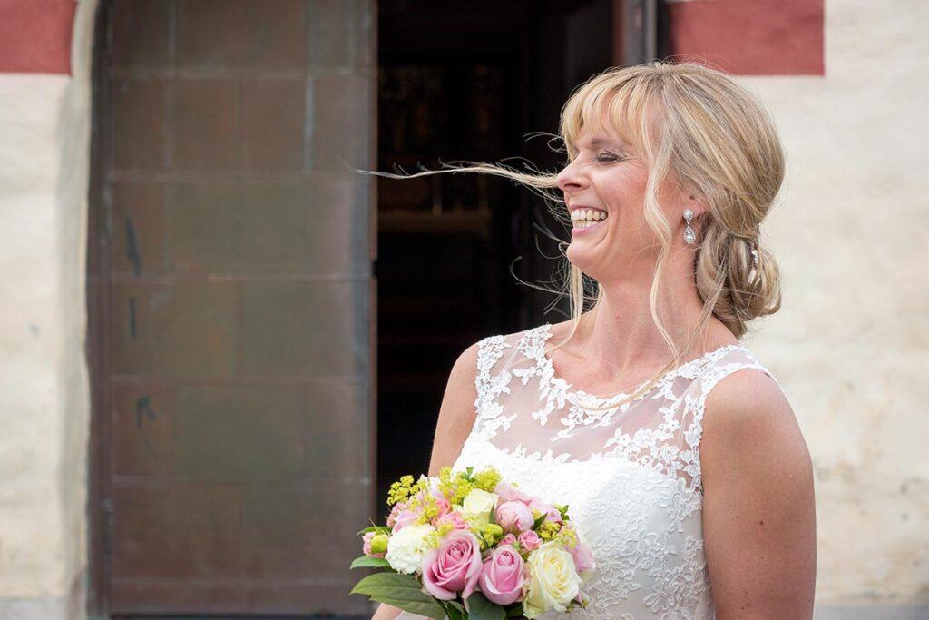 Bruden skrattar med bröllopsbukett i handen framför kyrkan