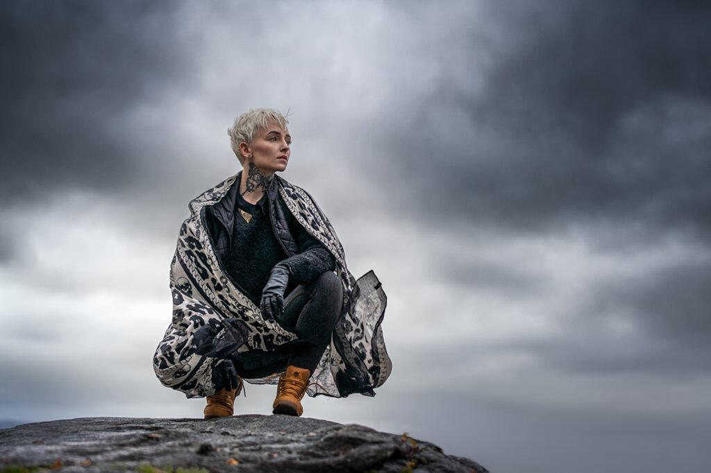 blond kvinna sitter på huk på en sten insvept i en sjal