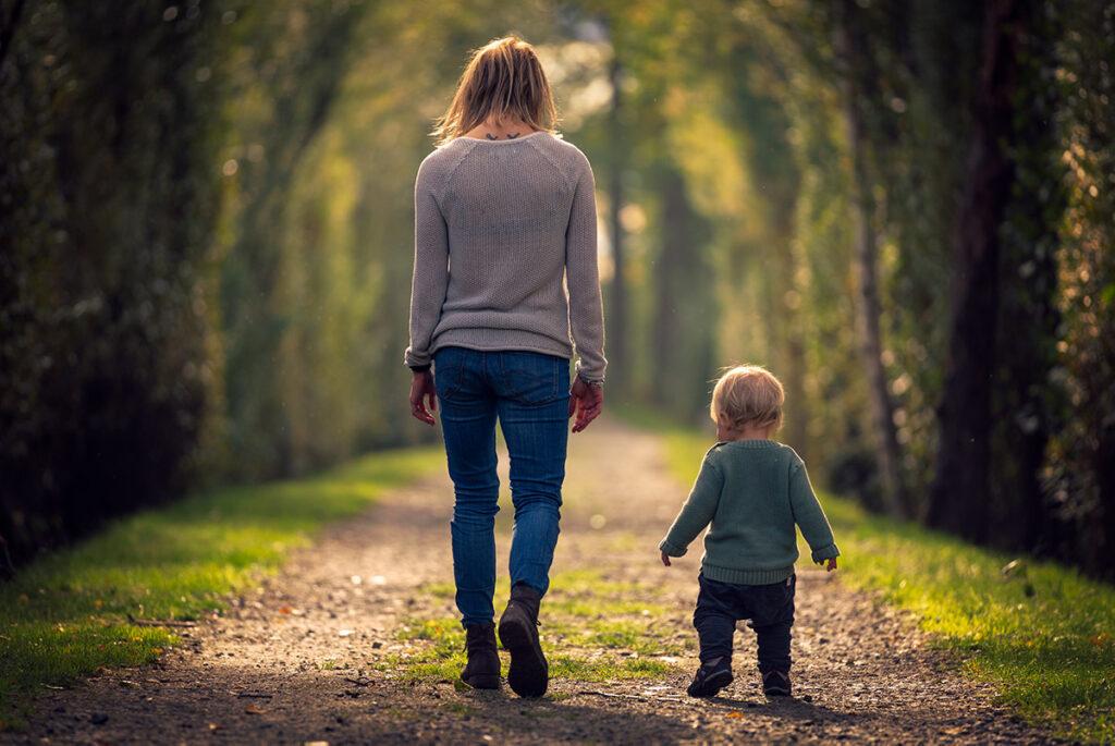 mor och son går på stig i en allé