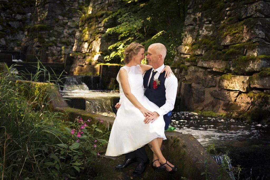 Bruden sitter i brudgummens knä vid älv