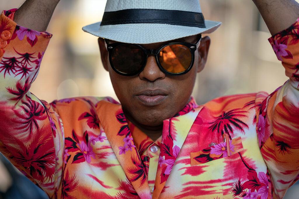porträtt av kille i hatt och solglasögon i färgglada kläder