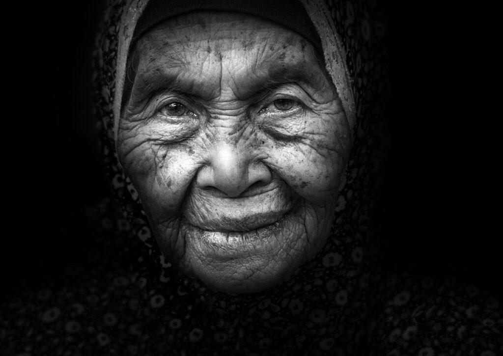 svart vitt porträtt av gammal kvinna omgiven av mörker