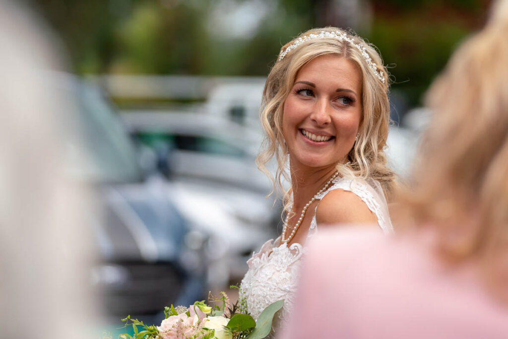 Leende nygift brud bland bröllopsgäster