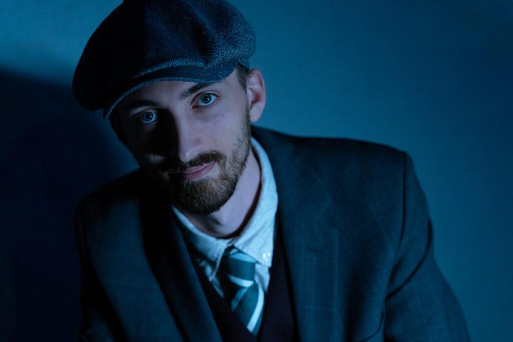 porträtt av man med basker i blått ljus