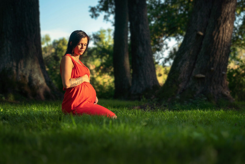 gravid foto av kvinna i öre kjol som sitter på knä i gräset och håller om sin gravida mage