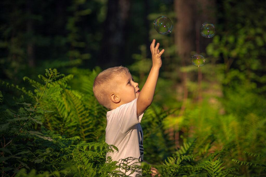 liten pojke jagar såpbubblor bland ormbunkarna