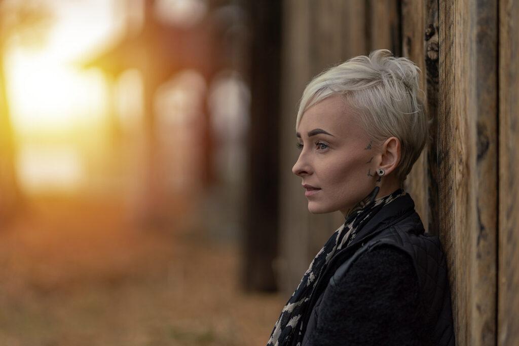 porträtt av kvinna som står vid en vägg med solljus som bryter in i bakgrunden