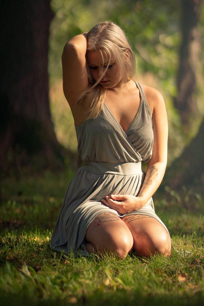 kvinna sitter på knä i gräset