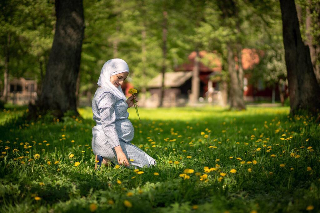 Arabisk gravid kvinna sitter på knä i gräset och plockar blommor