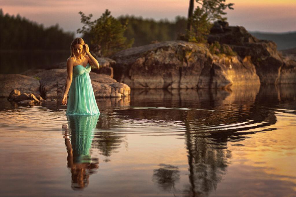 porträtt av kvinna i grön kjol som står i sjön