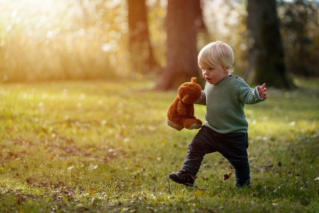 liten pojke springer i skogen med nalle i handen