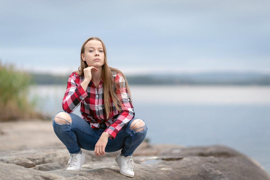 porträtt att kvinnlig tonåring som sitter på huk vid sjön
