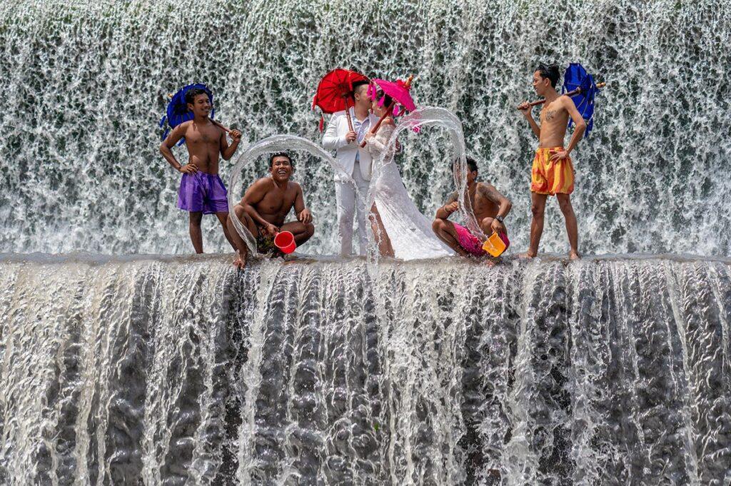 Bröllopspar står i ett vattenfall med män med paraplyer runt sig
