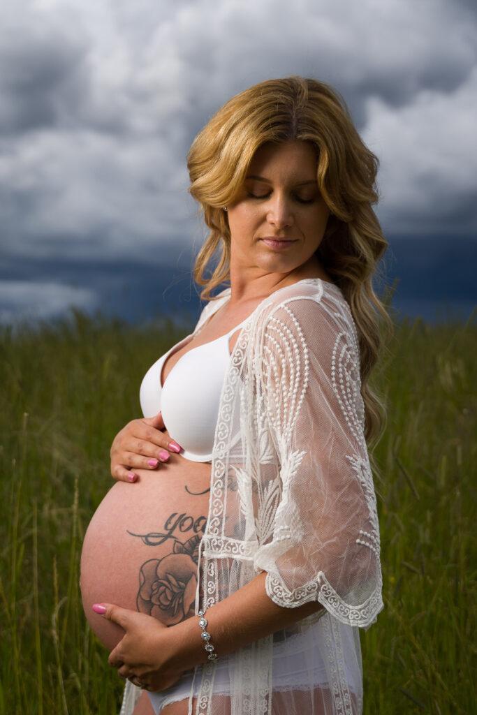 bild av gravid kvinna som står på en sommaräng med mörka hotfulla moln i bakgrunden Fagerås