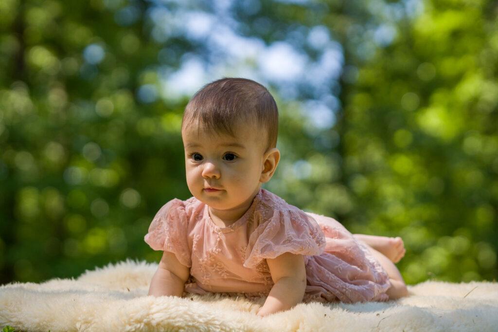 bild av baby som ligger på magen på en filt i gräset