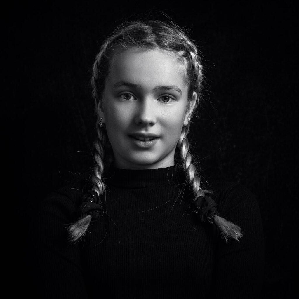 svart vitt studio porträtt av flicka i flätor