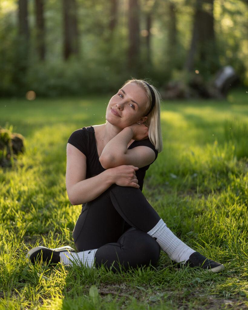 porträtt av ung kvinna som sitter med ben och armar i kors i gräset i solnedgången