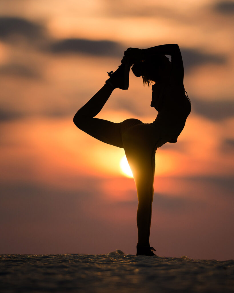 porträtt av kvinna i yogaställning i solnedgången