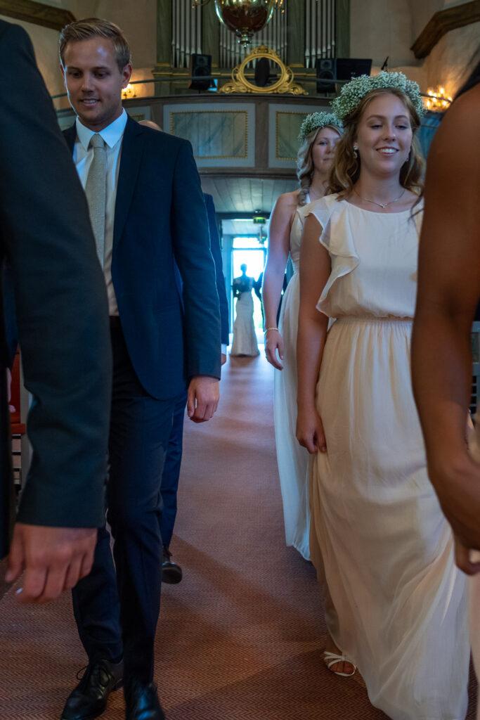 marskalker och brudtärnor går uppför altargången med bruden stående vid dörren i Grava kyrka Karlstad