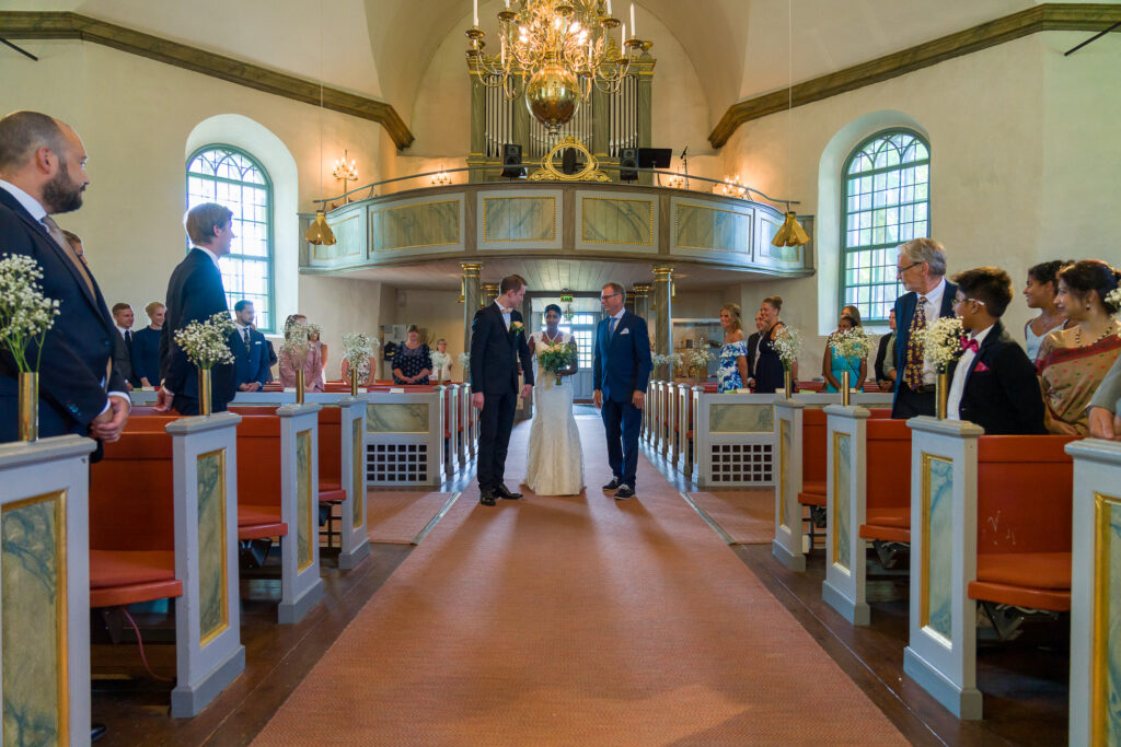 Brudens far lämnar över brud till brudgum