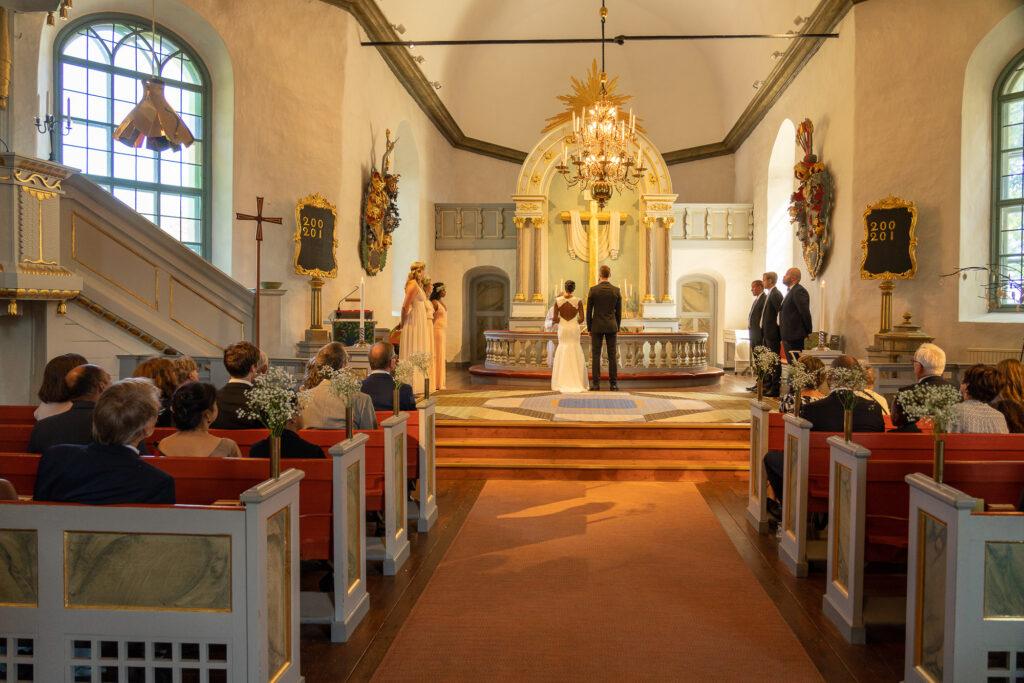 Bild av altargång och brudpar framför altare i Grava kyrka Karlstad