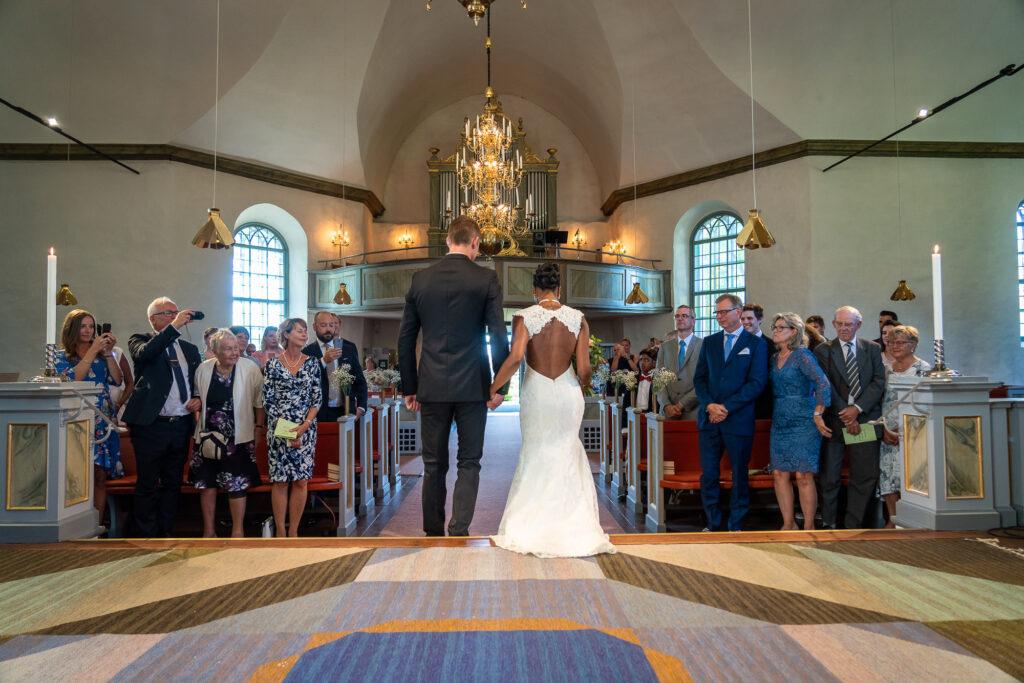 Bröllopspar som går ut ur kyrkan