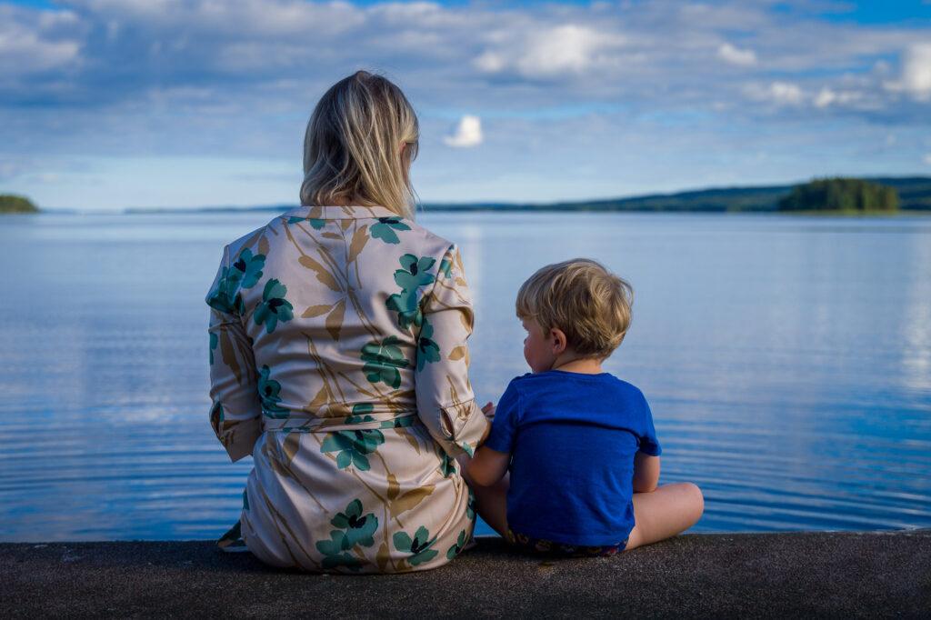 Mor och son sitter på en brygga vid Glafsfjorden