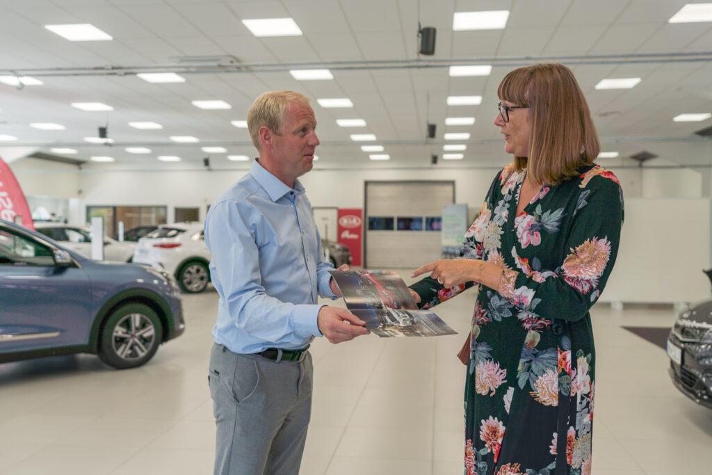 Personal på bilföretag pratar med kund