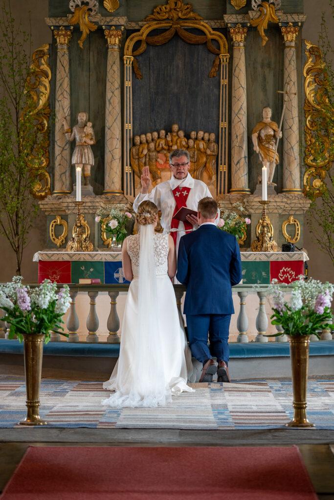 Bröllopspar på knä framför prästen i Karlanda kyrka Årjäng