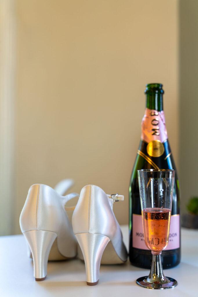 Brudens skor och champagneflaska på ett bord.
