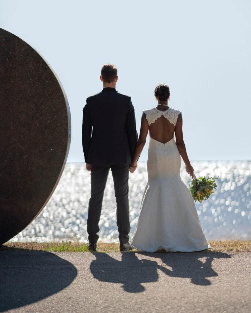 Bröllopspar står hand i hand med ryggen mot kameran vid Klarälven i Karlstad