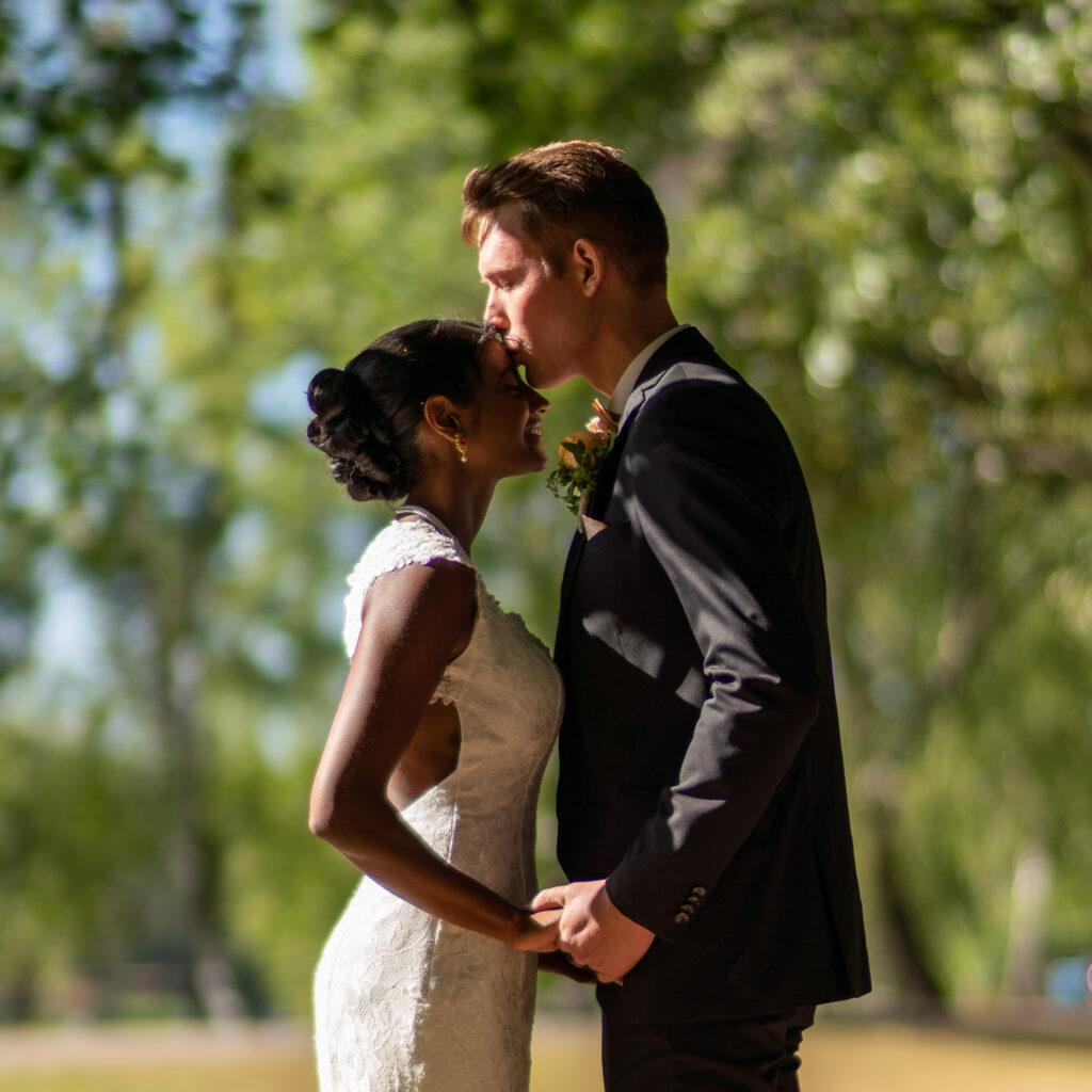 Brudgum kysser brudens panna i museiparken Karlstad