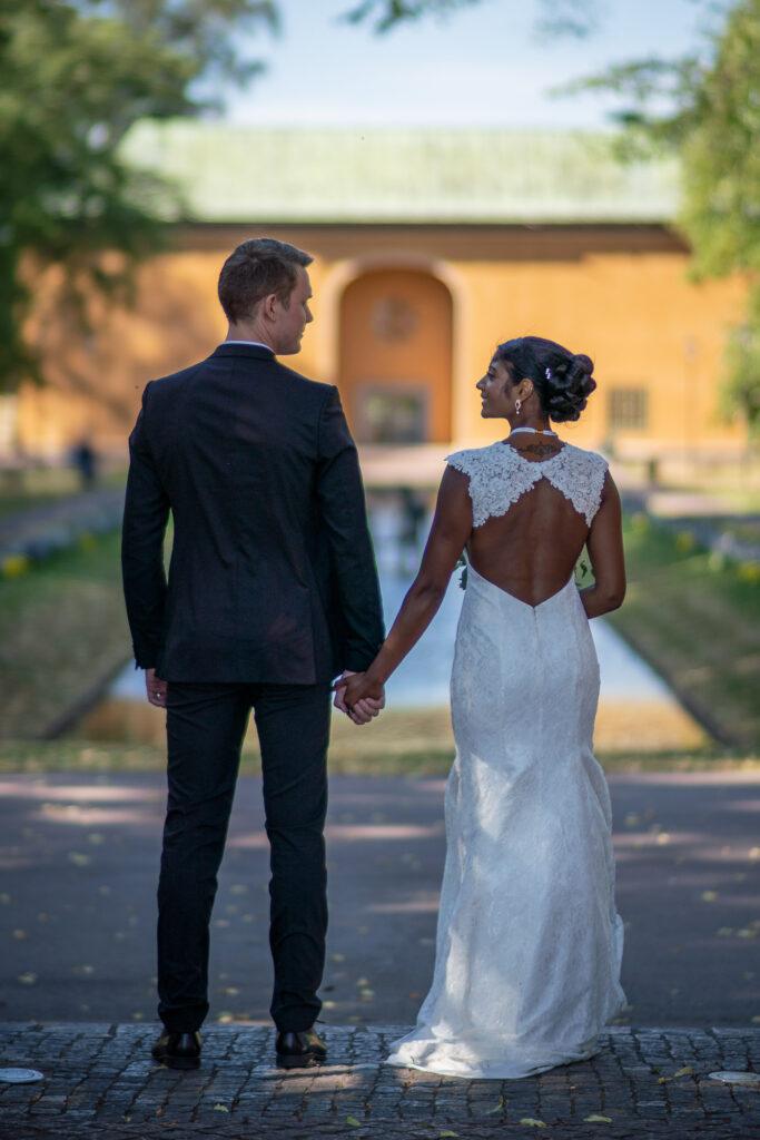 nygift bröllopspar håller varandras händer i museiparken Karlstad