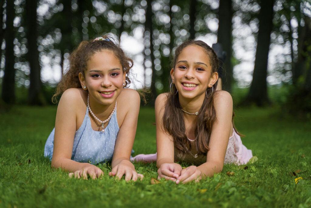 två tonåriga flickor ligger på gräset och ler mot kameran