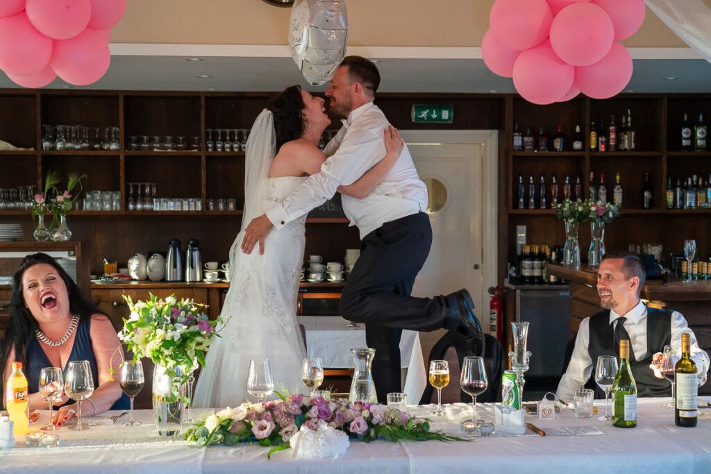 Brudgummen och bruden står på stol och har kul bland bröllopsgäster