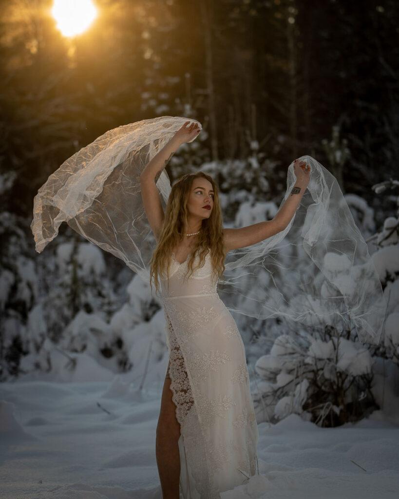 kvinna i vit kjol och vit sjal i vintrig natur