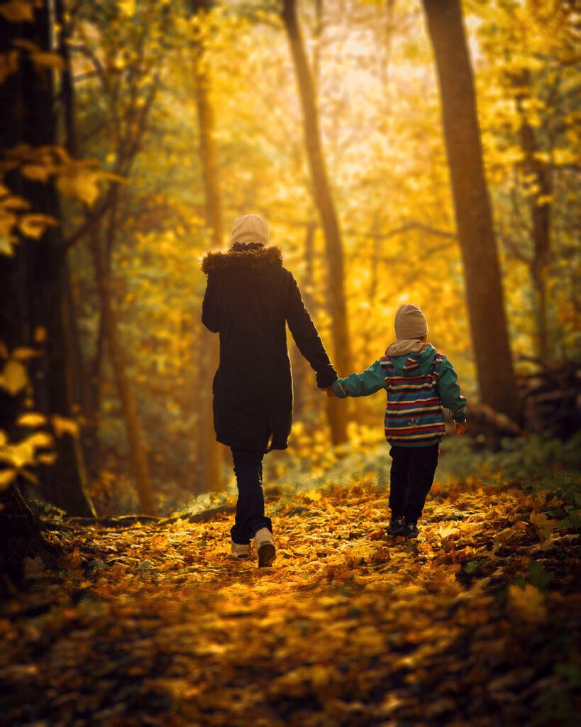 mor och son går hand i hand på stig i Alsters höstskog