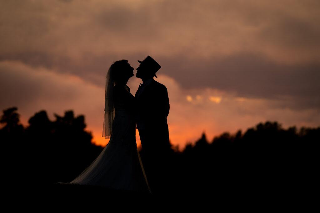 Silhuetten av ett bröllopspar vid solnedgång
