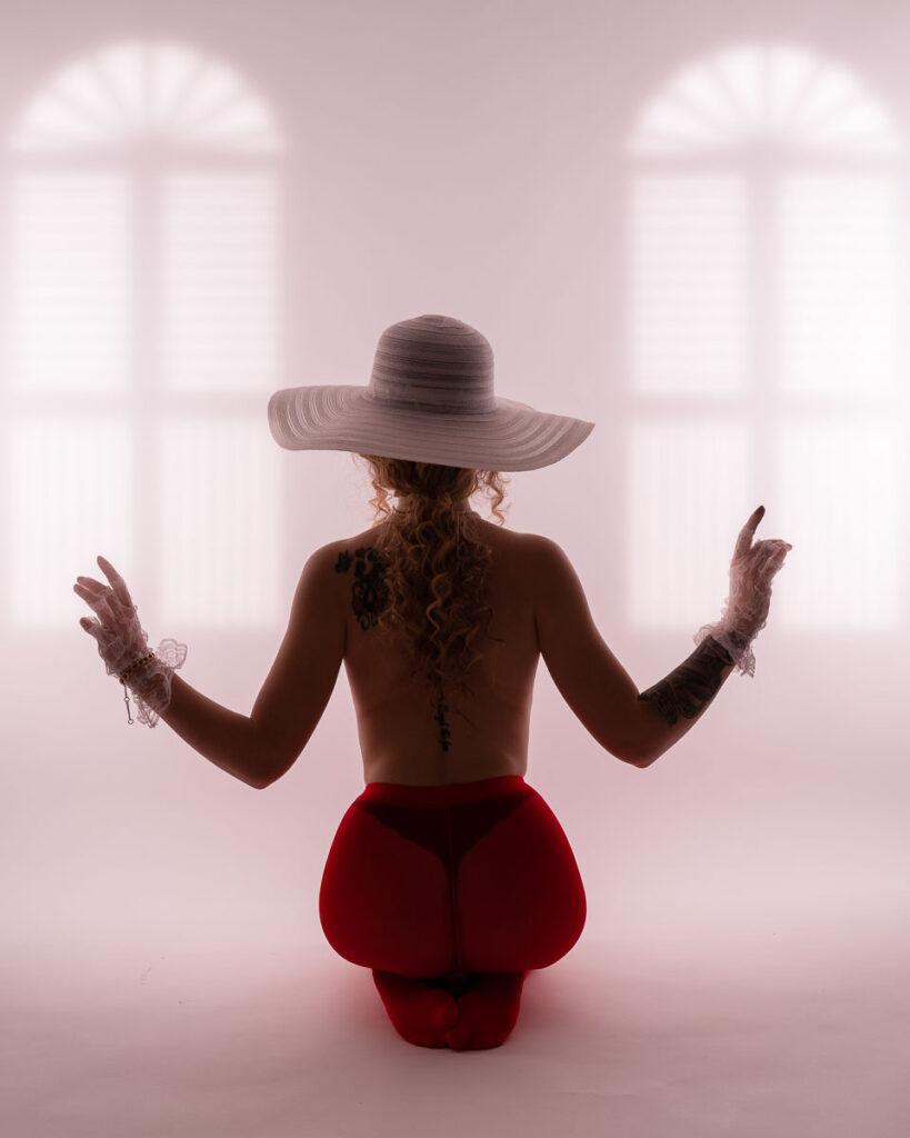 kvinna i bar överkropp, röda underbyxor och hatt i studion