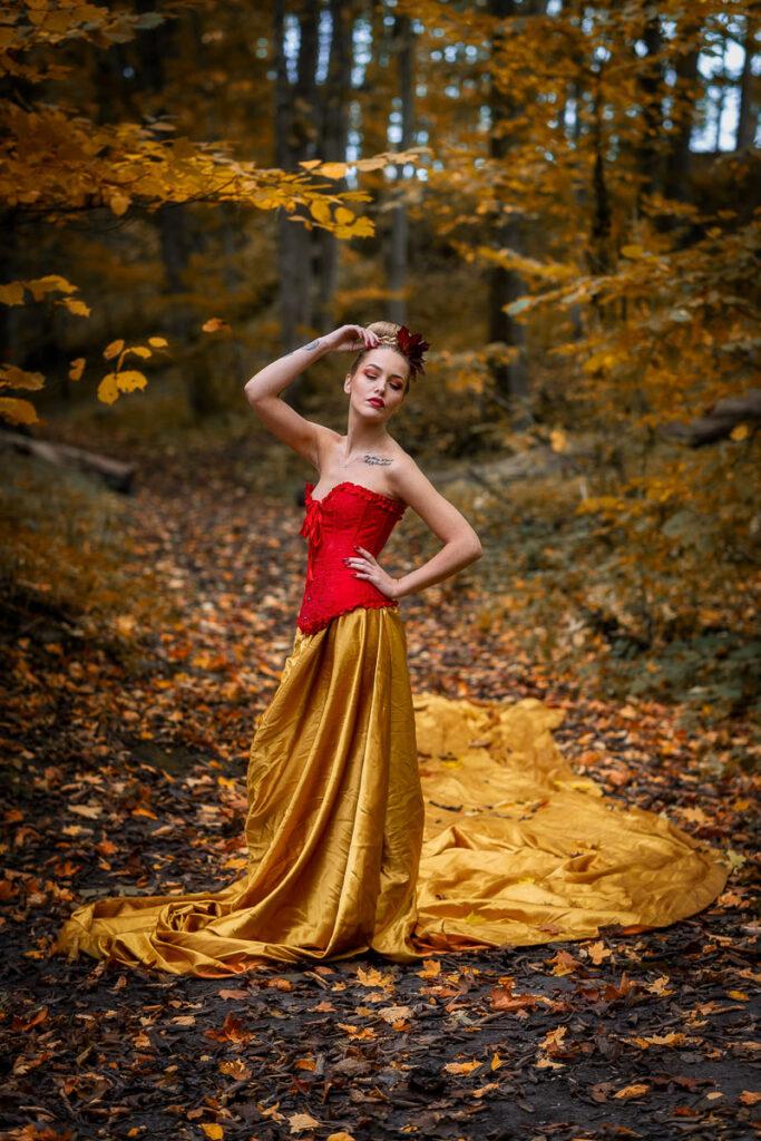 kvinna i gul kjol och röd topp i Alsters höstskog Karlstad