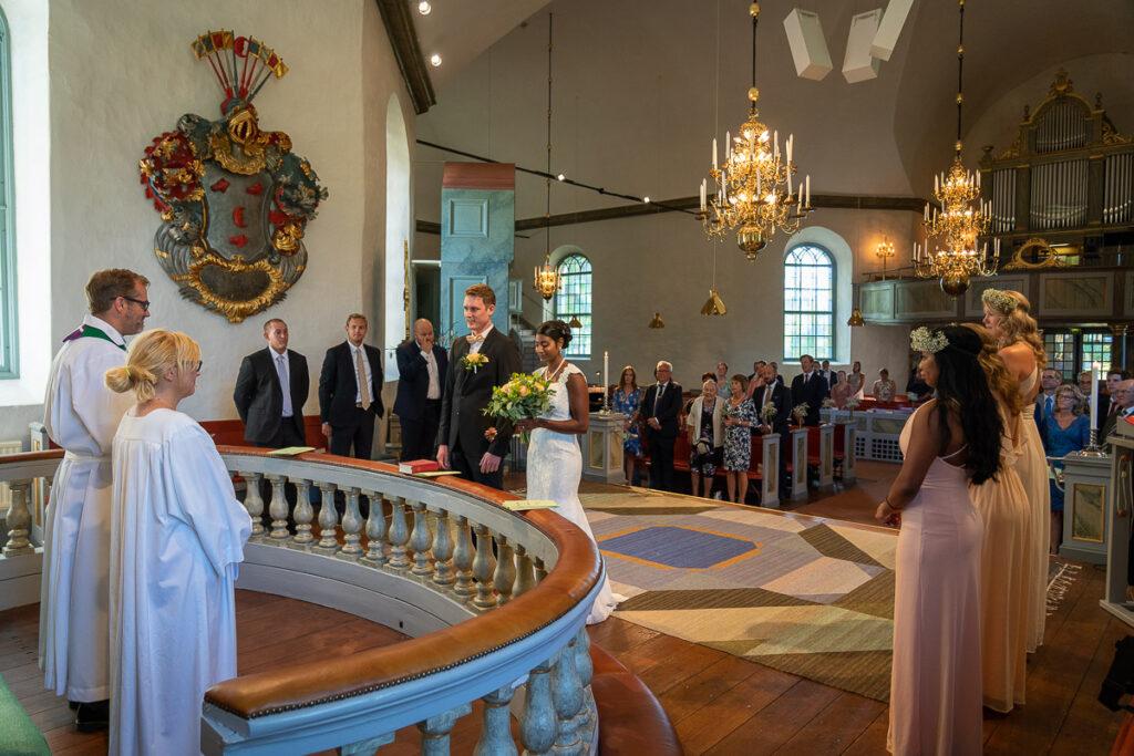 Präst och brudpar framför altare i Grava kyrka Karlstad